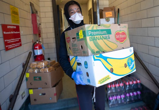 A worker carries food boxes for distribution at WestCare Wisconsin's food pantry.