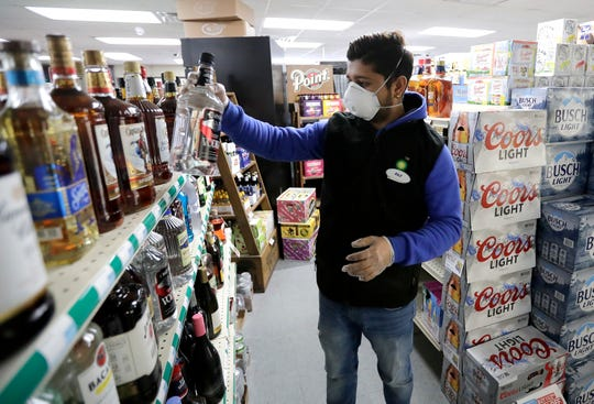 Weyauwega BP manager Rajan Panthi stocks dons an N95 mask and rubber gloves as he stocks liquor bottles  in Weyauwega, Wis.