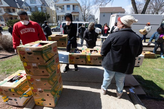 Food boxes are arranged for distribution at WestCare Wisconsin's food pantry on Wright Street in Milwaukee on Wednesday afternoon. WestCare organizers expected to serve about 200 people but about 600 showed up. The food boxes contained fresh produce, meat and other items.