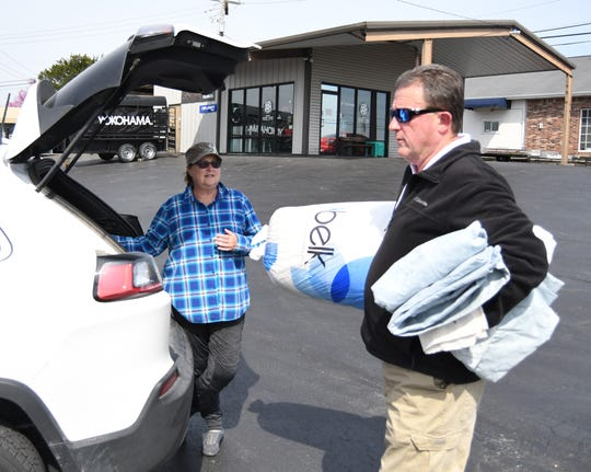 Mountain Home Mayor Hillrey Adams (right) collects donation items from Mary Carley of Mountain Home on Wednesday at PSI Tire. The City of Mountain Home, Spartan Mowers, and PSI Tires collected items earlier this week to benefit Jonesboro tornado victims.