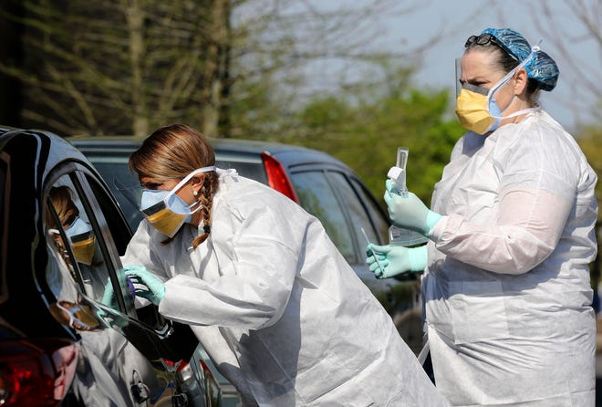 Nurse Mandy Stuckey reaches into a patient's vehicle window to do a COVID-19 test as fellow nurse Tonya Green, right, looks on at a drive-thru COVID-19 testing site at New Life Church in North Little Rock on Wednesday.