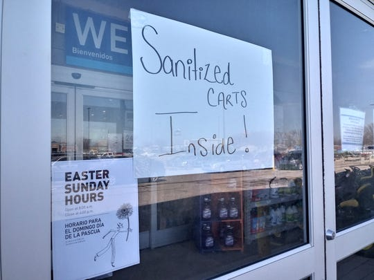 A sign saying there are sanitized shopping carts inside was on the door of Lowes Home Improvement store on Muncie on April 2. Stores across the county have implemented different policies to promote social distancing and halt the spread of COVID-19, but officials have said it may not be enough.