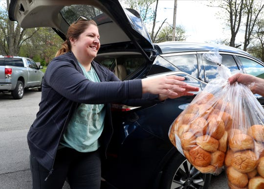 Ladawna Parham, with Nourish Food Bank grabed a bag of rolls as she picked up hot lunches at Olive Branch Church Murfreesboro, to distribute across town, on Wednesday, April 1, 2020.