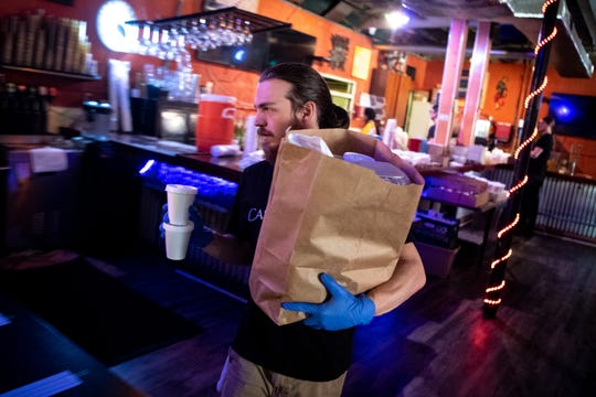 Sam Lowry carries an order read for pickup at Rosepepper Cantina in Nashville, Tenn., Wednesday, April 1, 2020. The East Nashville restaurant has adapted to the times by creating an efficient method for fulfilling take-out food and margarita orders.