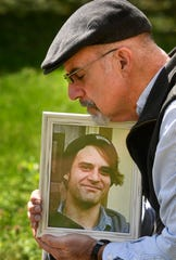 Mike Cronic holds a picture of his son, Clay Cronic, on April 1, 2020. His son died of a drug overdose after he lost his job and couldn't meet with other people in recovery due to government restrictions to fight the spread of the coronavirus.