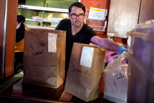 Christian Rada bags orders at Rosepepper Cantina in Nashville, Tenn., Wednesday, April 1, 2020. The East Nashville restaurant has adapted to the times by creating an efficient method for fulfilling take-out food and margarita orders.