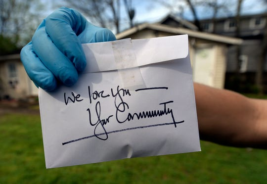 Thistle Farms volunteer Levi Hummon leaves a note before dropping off food and other supplies for clients and alumni recovering from addiction and trafficking on Thursday, March 26, 2020, in Nashville, Tenn.