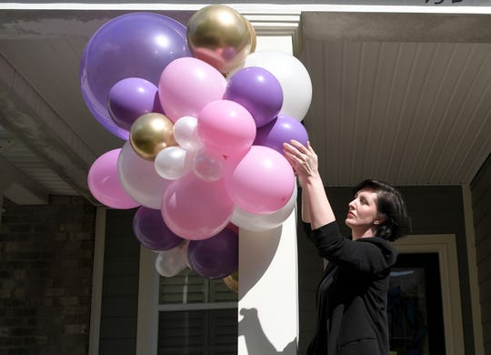 Camille Blinn installs a balloon arrangement for a birthday on a neighbor's front porch in Franklin on Wednesday, April 1, 2020. Her business, Glitter + Lightning, hit a snag with the coronavirus, but Blinn found a way to make people happy by offering balloon arrangements for her neighbors.