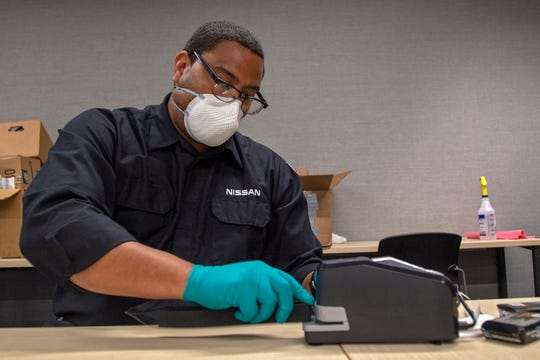 Nissan employee Jason Ballard attaches elastic to foam headband in an office inside the company's Smyrna machine shop.
