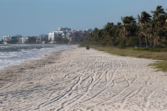 Naples police patrol the beach north of the Naples Pier on April 1.