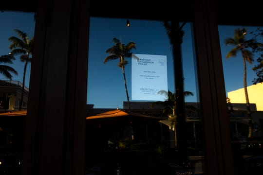 A sign posted at Bistro 821 lets customers know that the restaurant is still open, but only for carry-out business, on Fifth Avenue South in Naples on March 30.