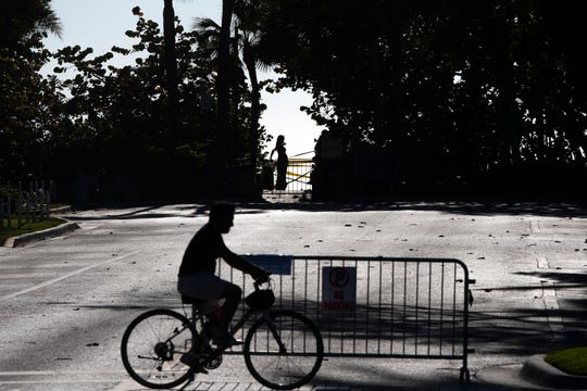 A cyclist passes a beach entrance off Broad Avenue on Wednesday in Naples.