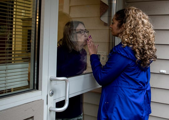 """JoAnn Poulton presses her hand up to glass door to say goodbye to her mom, Kathy Poulton who leans in to kiss her hand. Kathy is a resident at the Inn at Chapel Grove, a senior living facility in Heath and is living with dementia. In some ways, JoAnn thinks her mom having dementia is easier for her in this time, so she doesn't get scared, but also knows her mom doesn't understand why she can't enter the building and give a hug. """"Its hard,"""" she said. """"Every week we lose a little more of her."""""""