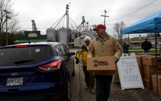 Mark Morscher (front) and Ken Cation (back) load a box of food in to a car at a drive up food pantry set up at the South Street Depot. The pantry serves Denison food preparers and some Granville restaurant employees facing layoffs or reduced hours amid the stay-at-home order in Ohio.