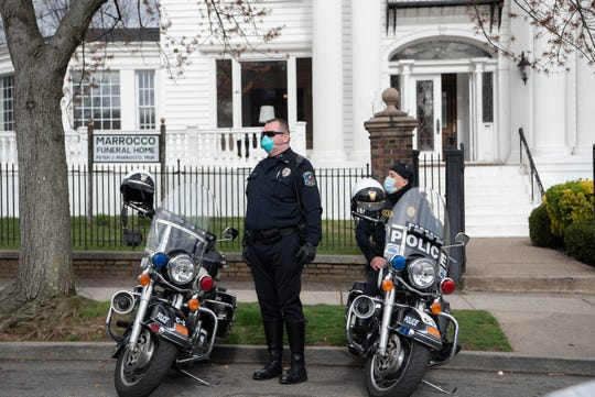 Passaic police officers waiting to escort a funeral procession.