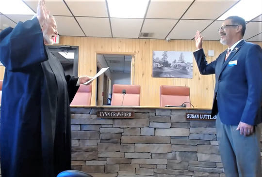 """Keeping their six-feet distance, 12th Judicial District Judge Daniel Bryant administers the oath of office to Ruidoso Councilor Rafael """"Rifle"""" Salas."""
