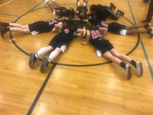 Eighth graders on the Discovery Middle School girls basketball team kiss the 'D' at the center of the court after their final home game.