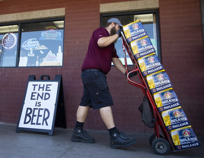 Colton Williams with Crescent Crown Distributing, delivers beer to Tops Liquors in Tempe, Ariz., on April 2, 2020.