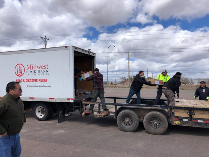Workers with the Navajo Housing Authority and Midwest Food Bank work to unload a truck of food boxes in Window Rock, Arizona.