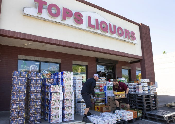 Chris Yahne, left, and Colton Williams, with Crescent Crown Distributing, deliver beer to Tops Liquors in Tempe on April 2, 2020. Tops Liquors has seen an increase in sales in the last two weeks.
