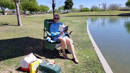 La residente de Phoenix Sue Castelletti disfruta de un libro bajo la sombra en el Steele Indian School Park en el centro de Phoenix el 24 de marzo de 2020.