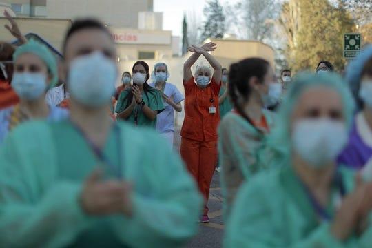 Trabajadores sanitarios aplauden a la gente que, desde sus casas, muestra su apoyo al personal que trabajaba para contener el brote de coronavirus.