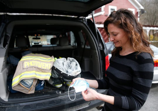 Pleasant Valley Fire Department commissioner Melissa Lawlor shows one of the masks that the department issued out to its first responders at her home in Pleasant Valley on April 2, 2020.
