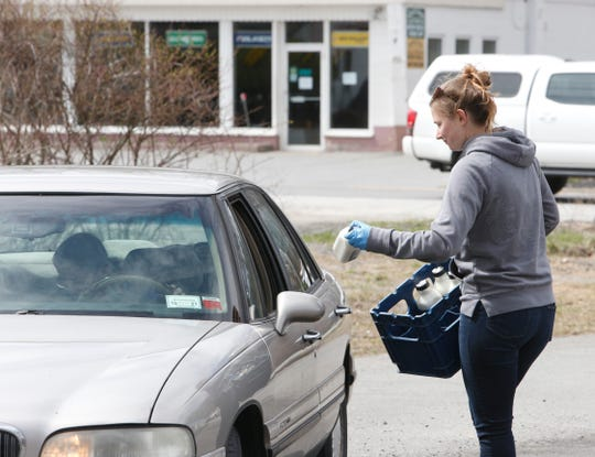 Sarah Dowling of Dutchess Creamery distributes free milk at Dairy Creme in Rhinebeck on April 2, 2020. The dairy's cows are producing milk that the management would rather give to locals in need than to destroy it.