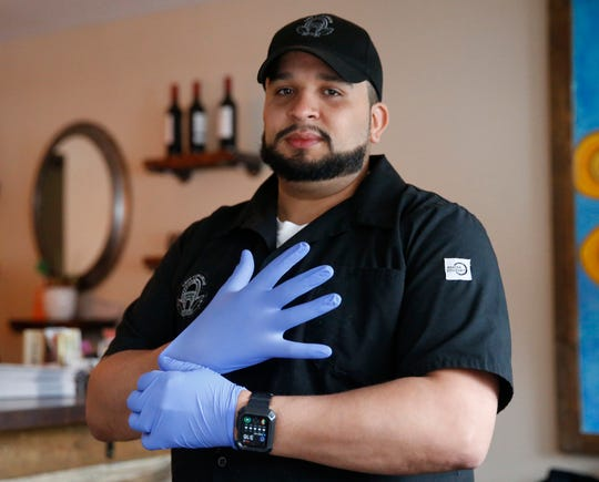 Phli Cordero, owner of Cafe Con Leche puts on a pair of rubber gloves before handling a customer's order at the cafe in the Village of Wappingers Falls on April 2, 2020.