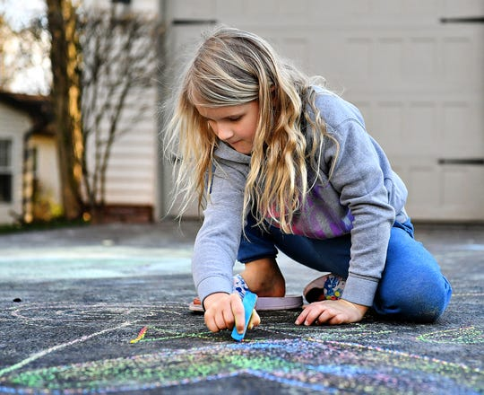 Stella Snelbaker, 7, chalks cheerful drawings on her driveway in Manchester Township, Wednesday, April 1, 2020. Dawn J. Sagert photo