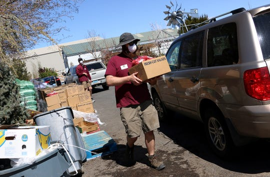 Hayden Wilkinson helps distribute food provided by the Plan B Ranch at Rail City Garden Center in Sparks on April 2, 2020.