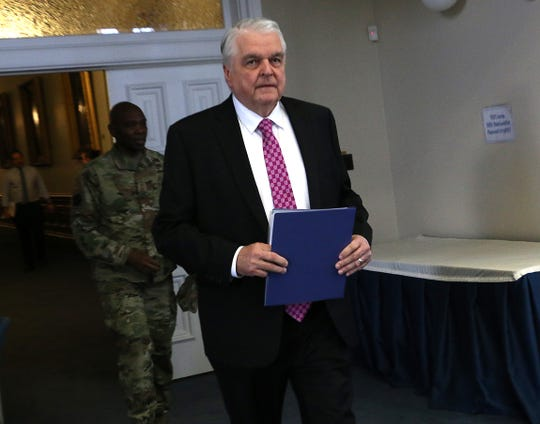 Nevada Governor Steve Sisolak enter the room for a press conference about the COVID-19 pandemic in the Old Assembly Chambers in the Nevada State Capital Building in Carson City on April 1, 2020.