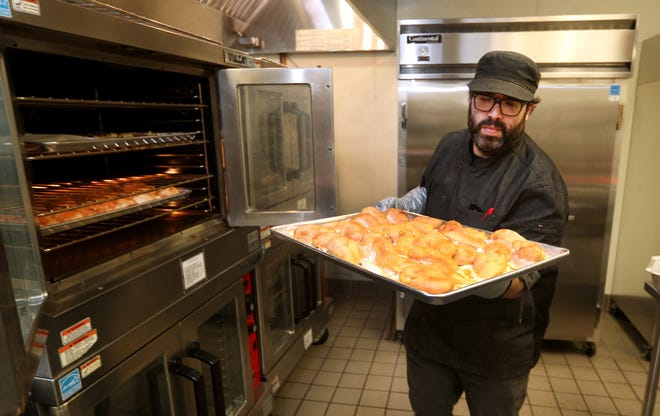 Eli Barashi, owner and chef of Inspired Catering, pulls chicken from the oven in 2020. Barashi and his staff prepared 600 meals for Passover using the kitchen at Beth Sholom.