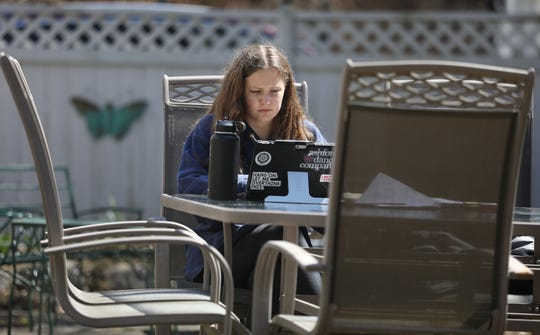 Our Lady of Mercy ninth grader Molly Topa works on her theology class assignment while doing her distant learning with the school while enjoying the sunshine on the patio in the backyard of her Rochester home Wednesday, April 1, 2020. Due to the coronavirus pandemic, all schools in Rochester and Monroe County, are closed, forcing schools and students to adapt to full-time on-line learning.