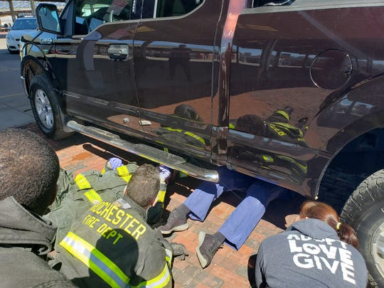 First responders works to free, Zeke, a 2-year-old beagle, from beneath his owner's pickup Thursday morning at the Rochester Public Market.