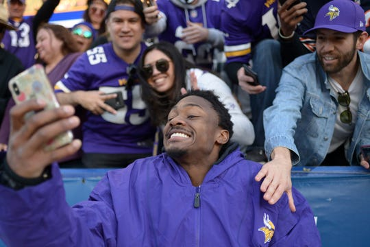 Minnesota Vikings wide receiver Stefon Diggs (14) takes celebratory selfies with the phones of fans after the Vikings beat the Los Angeles Chargers.