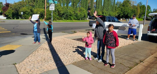 Families wave to teachers from Lassen View Elementary School who formed a parade as a way to interact with their students on April 2, 2020 since the coronavirus pandemic moved classes to online learning.