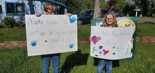Lassen View Elementary school second grader Robert Hoke (left) and first grader Abigail Hoke show signs for their teachers at the corner of Loma Vista Drive and Bechelli Lane on April 2, 2020.