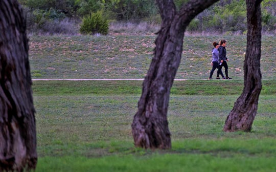 People walk along the KOA trail near Lake Nasworthy on Wednesday, April 1, 2020. San Angelo city leaders ordered the trail closed to recreational access effective at 12 a.m. on Thursday, April 2, 2020.