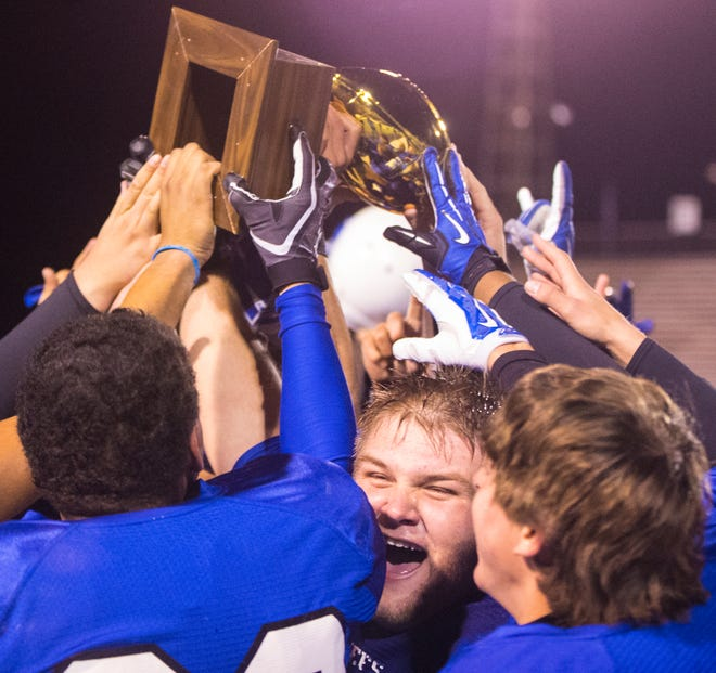 """Lake View High School's D.J. Schlather screams """"We did it!"""" as he joins his teammates raising their Class 5A Division II bidistrict playoff trophy after defeating Canyon 26-21 in Big Spring on Nov. 14, 2014."""