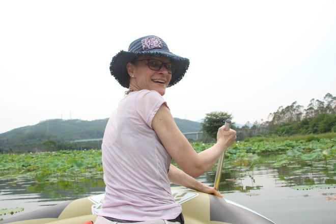 Veronica Daugherty paddles through a lotus field in Guangdong Province, China.