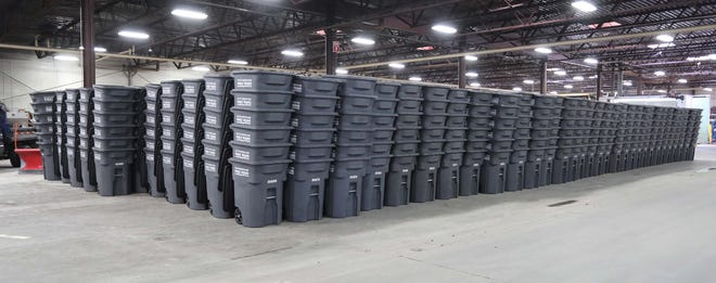 Stacks of garbage carts appear Wednesday, April 1, 2020, at the Department of Public Works building in Sheboygan, Wis. Ones with black lids are meant for garbage and the ones in blue are meant for recyclables.