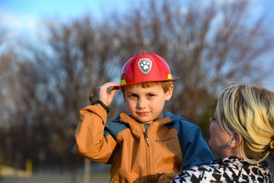 Luke Taverna wears a plastic fireman hat while watching the local fire station parade past his neighborhood on Wednesday, April 1, on 69th Street in Sioux Falls.
