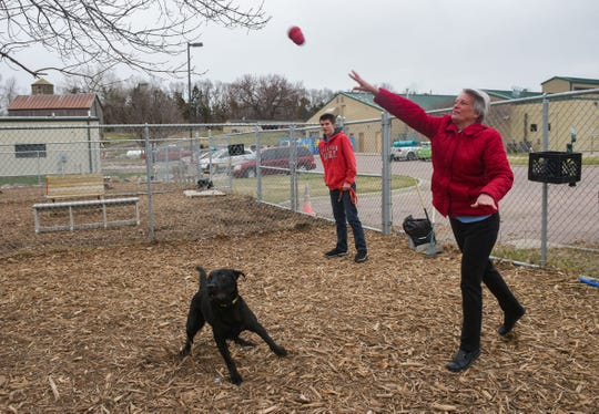 Adam and Stephanie Carlson play with a black lab named Rocky they adopted via curbside adoption on Thursday, April 2, at the Sioux Falls Area Humane Society.