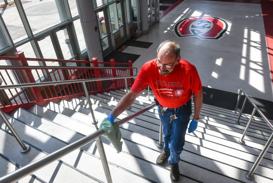 Lead general maintenance worker Bob Dubbin cleans railings on staircases at the entrance to the Herb Brooks National Hockey Center Wednesday, April 1, 2020, at St. Cloud State University.