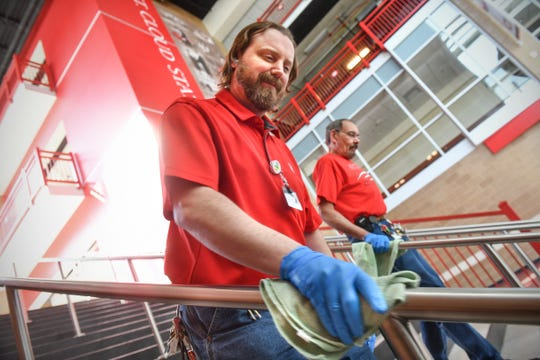 Building services foreman Brian Toutges and lead general maintenance worker Bob Dubbin clean hand railings near the entrance to the Herb Brooks National Hockey Center Wednesday, April 1, 2020, at St. Cloud State University.