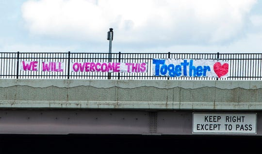 """A sign on the 600 North overpass of northbound on I-15 says """"We Will Overcome This Together"""" in Salt lake City, Tuesday March 31, 2020. (Rick Egan/The Salt Lake Tribune via AP)"""