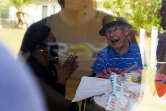 Harry Toban, opens his birthday presents as his family stands outside the window of his nursing facility on Thursday, April 2, 2020, in Vero Beach. Toban celebrated his 95th birthday separated from his wife of 70 years, Jackie Toban, because the facility, Palm Garden of Vero Beach, closed it to visitors to protect residents from exposure to COVID-19.