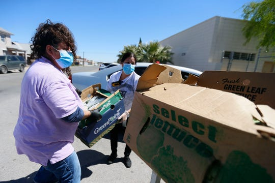 Maria Galaviz, left, and Stephanie Jones, right, take in a food donation at the Opportunity Center for the Homeless Thursday, April 2, in El Paso. Homeless shelters are receiving less donations because of the stay-at-home order in El Paso in response to COVID-19.