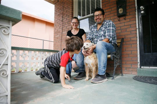 Anita Volf, left, Xavier Gonzales, right, their son Karlo Gonzales, center, and their dog Maya on their porch in front of their home Wednesday, April 1, in El Paso. Anita was recently laid off from her job as an assistant general manager at a hotel and Xavier is out of work as a musician since restaurants and bars have closed.
